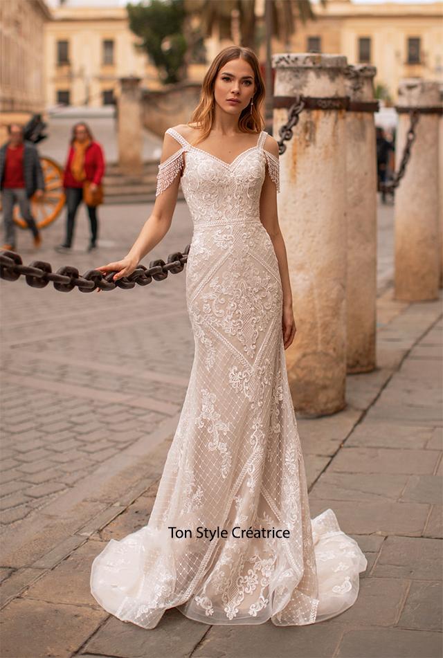 Robe de mariée près du corps brentelle et manche perlé, le dos à un lassage bas mais qui est doublé. Robe en dentelle.